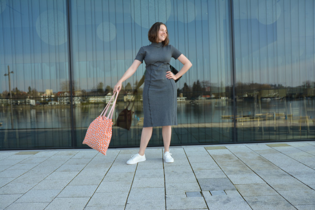 Woman wearing a grey rib knit dress and white sneakers. She is swinging an orange tote back and smiling. Behind her is a large window showing reflections of a lake.