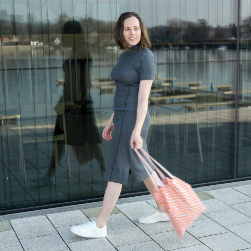 Woman wearing grey dress and white sneakers walking along a large window. She is swinging an orange tote bag and smiling.