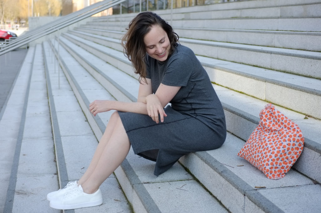 Woman wearing grey dress and white sneakers sitting on a flight of grey stairs. Next to her is an orange tote bag. She is smiling and looking down.