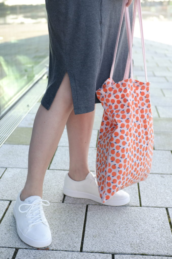 Close-up of the legs of a person wearing a grey dress and white sneakers, holding a tote bag with an orange pattern.