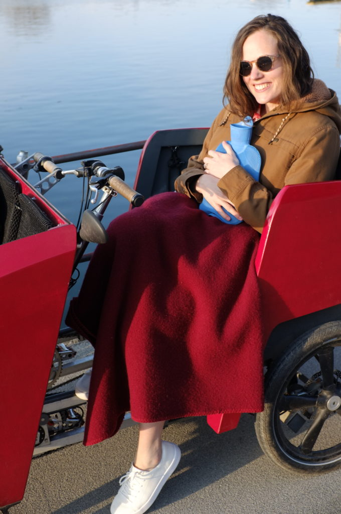 The photograph shows a woman wearing sun glasses sitting in a red vehicle. She is wearing a grey jacket, white sneakers and is wrapped in a red blanket. She is clutching a blue hot-water bottle and smiling. Behind her a body of water is visible.